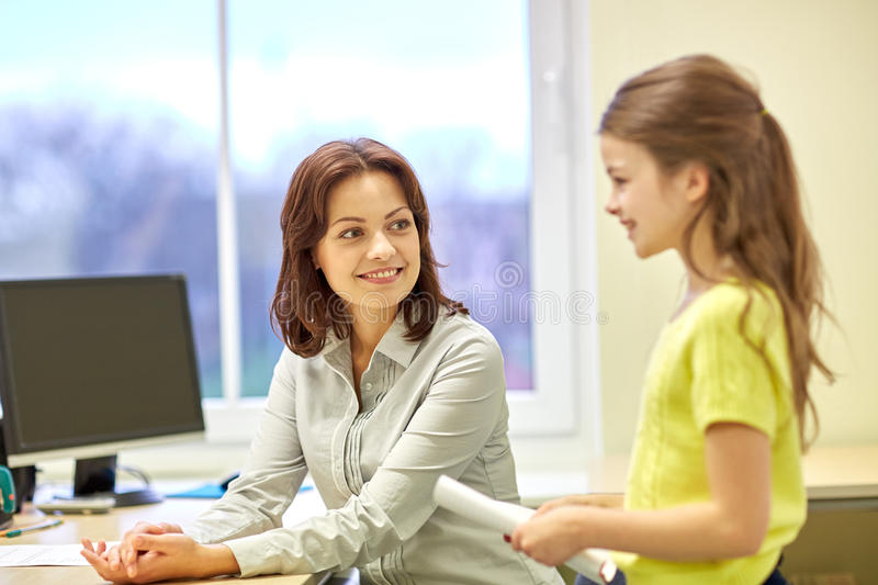 School girl with notebook and teacher in classroom royalty free stock photo
