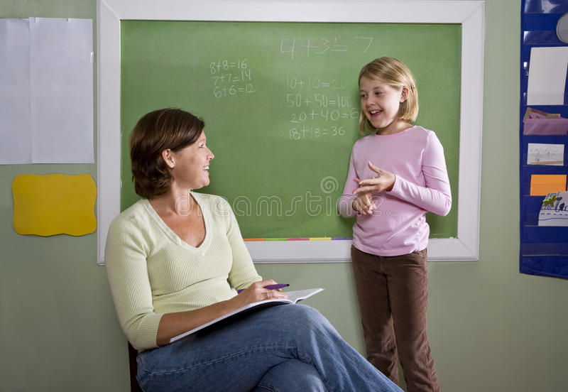 Download School Girl And Teacher By Blackboard In Classroom Stock Photo - Image: 15845934
