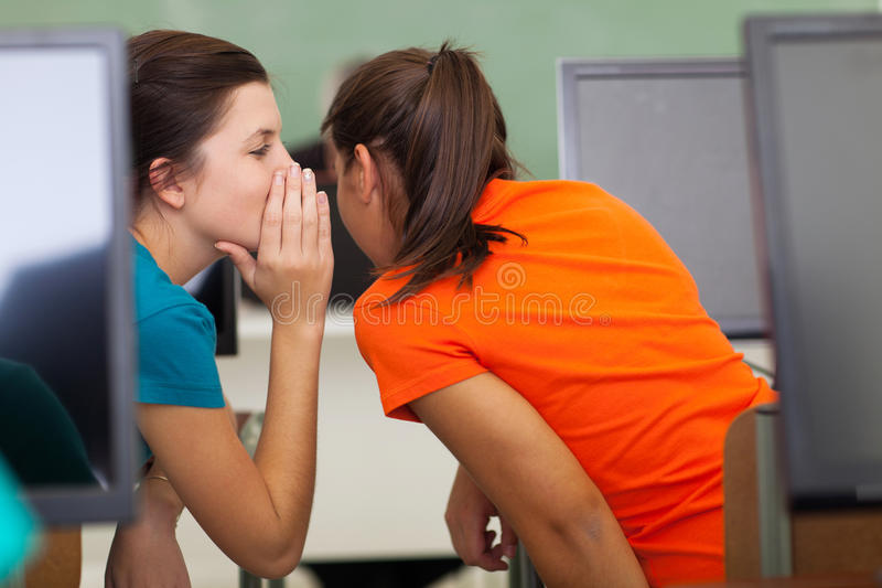 School girls gossiping. High school girls gossiping in class during a lesson stock images