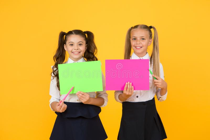 School girls show poster. Presentation poster copy space. Children presenting own projects. Explain main point. Girls. School uniform hold poster. Visual royalty free stock photography