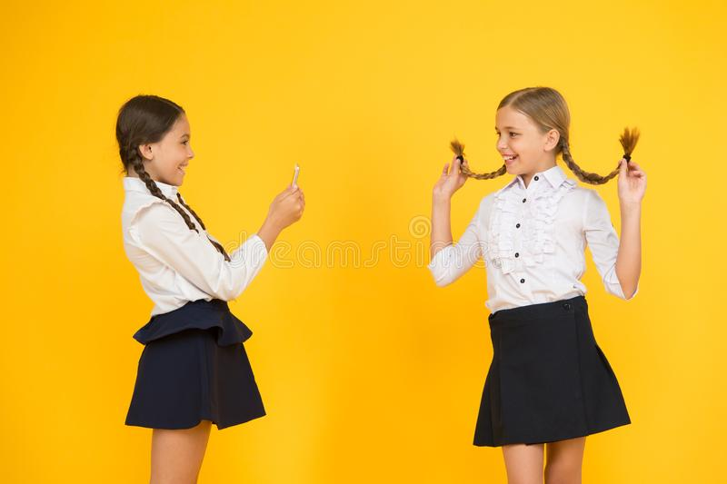 School girls use smartphone to take photo. Girls school uniform. Dont give anyone your password address or any. Information about your family. Life online stock photo