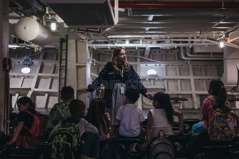 School group listening to the guide during a tour inside Intrepid Sea and Air Museum, New York, USA. stock photo