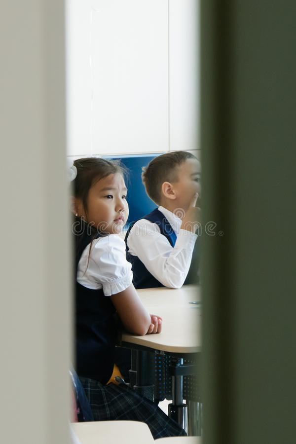 School. Half-open doors of classroom. It can be seen how girl and boy in school uniform sit at desk and attentively listen to stock image