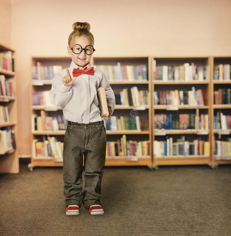 School Kid in Library, Child in Glasses, Girl with Book. School Kid in Library, Child in Glasses with Book, Little Girl Student Finger Point Up, Bookcase Shelves royalty free stock photos
