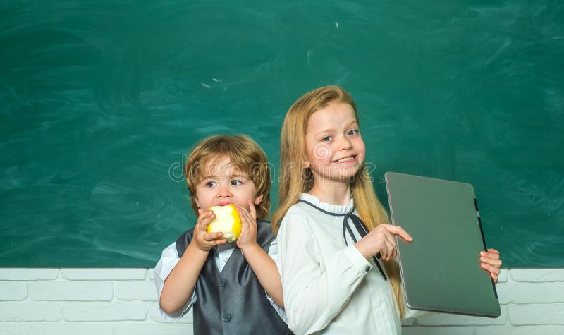 School kids against green chalkboard. Girl and boy with happy face expression near desk with school supplies. Teacher stock images