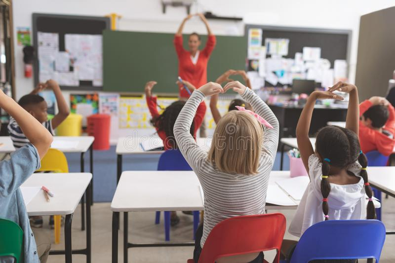 School kids with arms up playing in the classroom at school stock photos