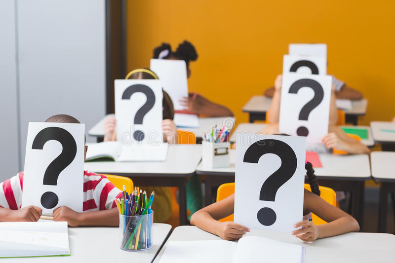 School kids covering their face with question mark sign royalty free stock photography