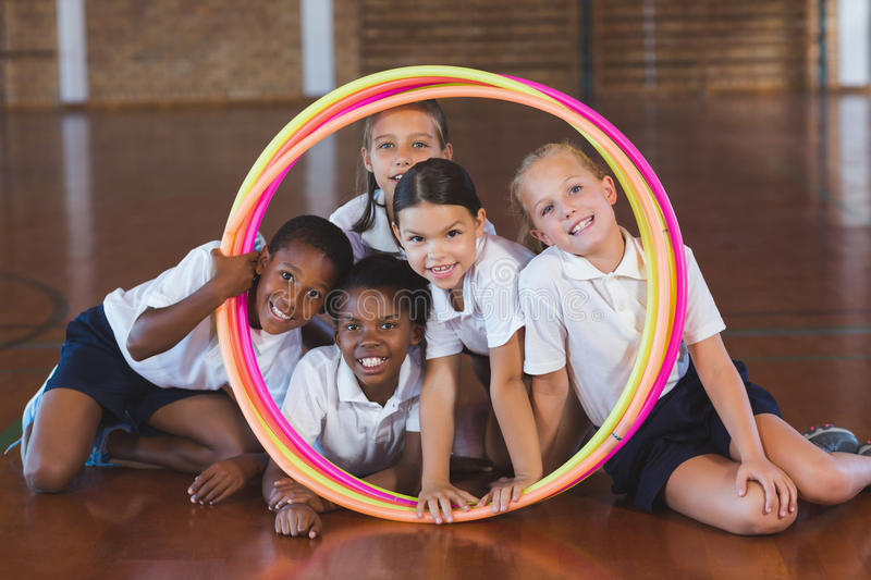 School kids looking through hula hoop in basketball court stock image