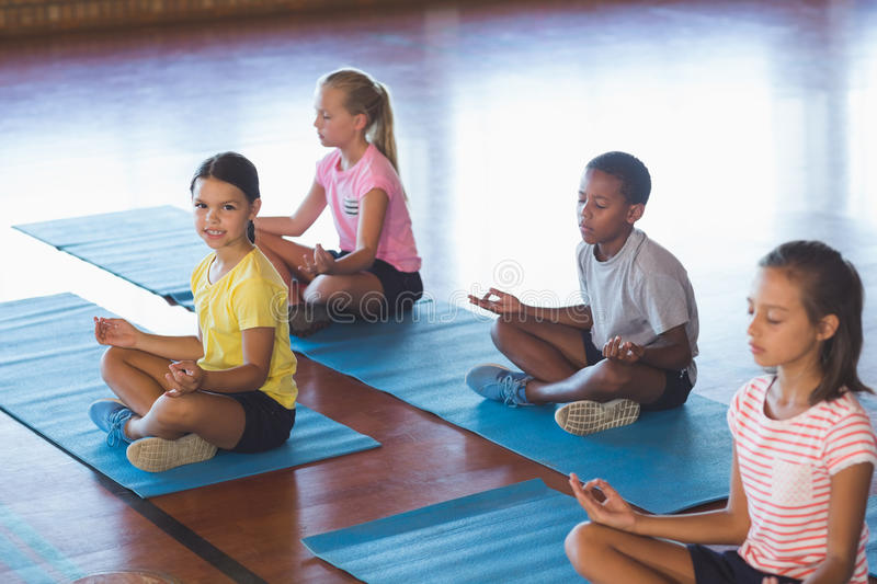 School kids meditating during yoga class stock images