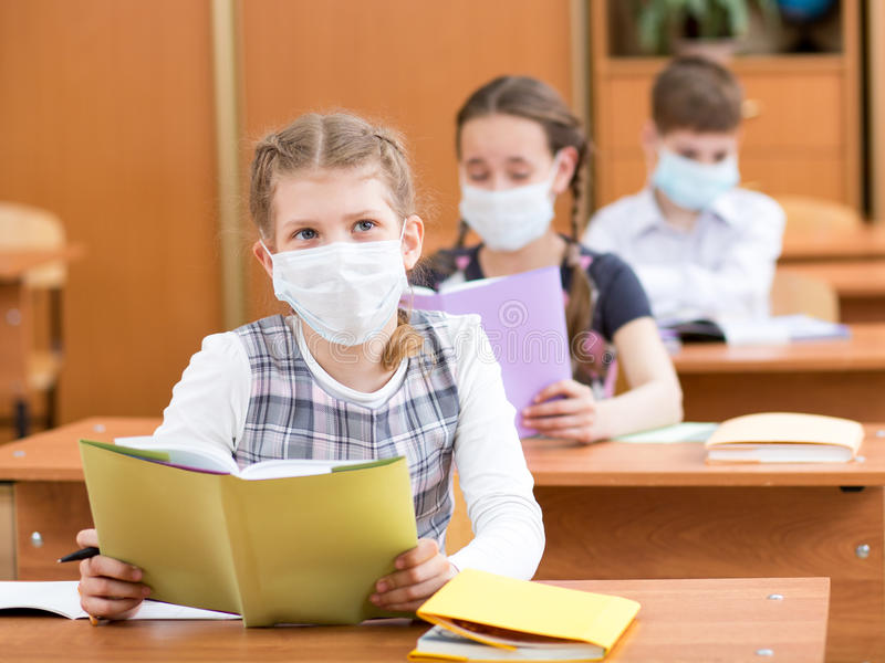 School kids with protection mask against flu virus. At lesson stock image