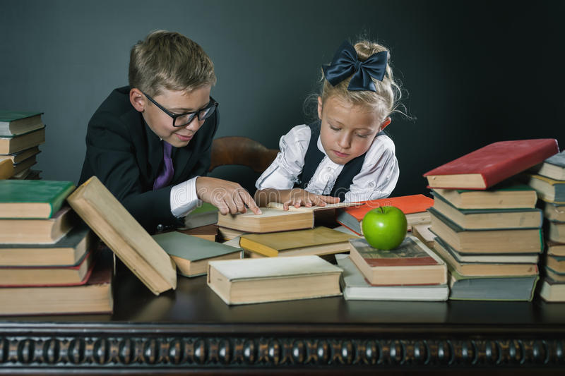 School kids reading a book at library. Motivate your child to study boring subject. Table with many books and one green apple. Children dressed in school stock image