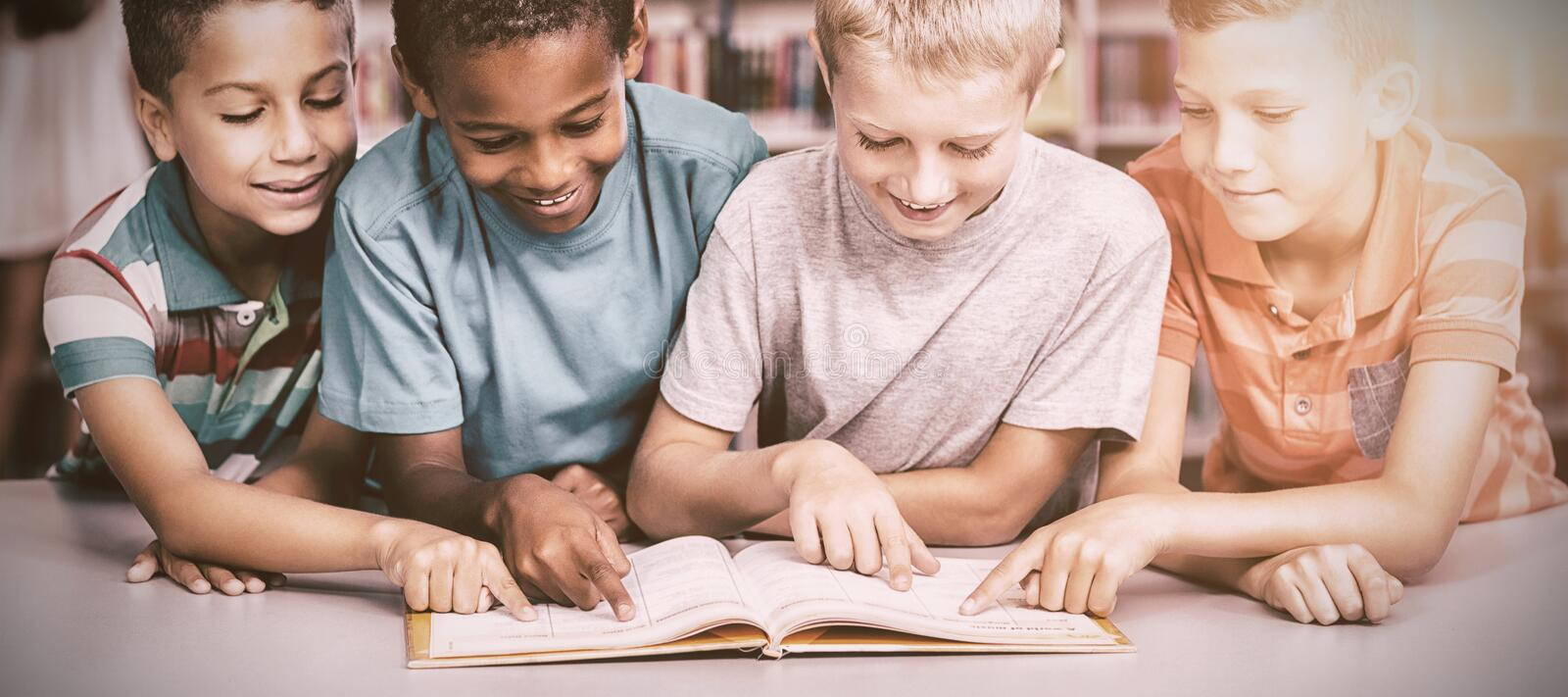 School kids reading book together in library stock image