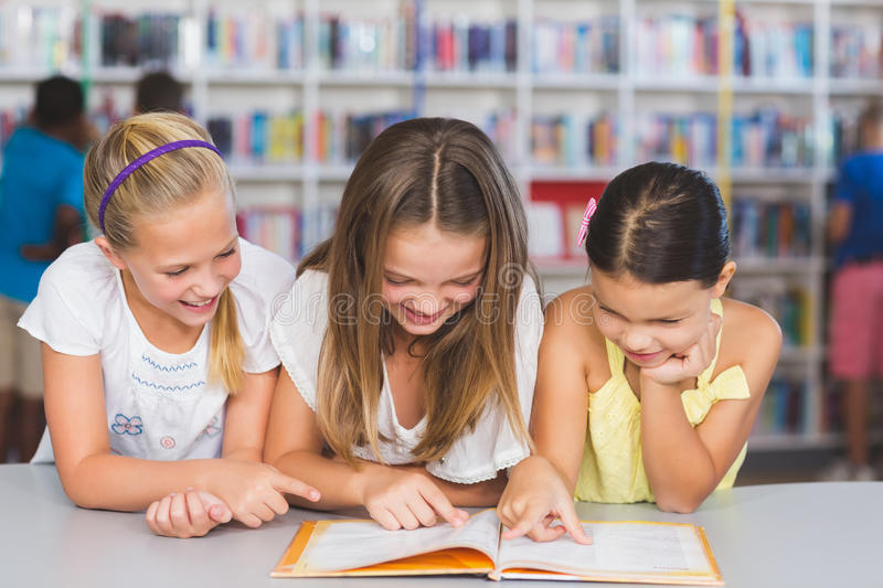 School kids reading book together in library royalty free stock photos