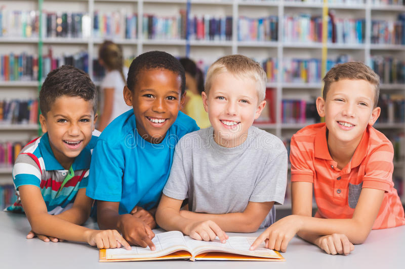 School kids reading book together in library stock images