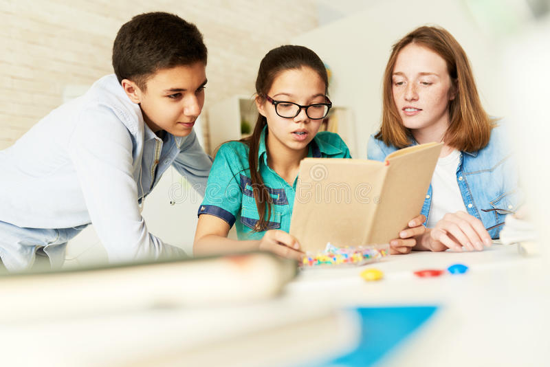 School Kids Reading Book Together. Portrait of three teenage kids reading book together in classroom during lesson royalty free stock photo
