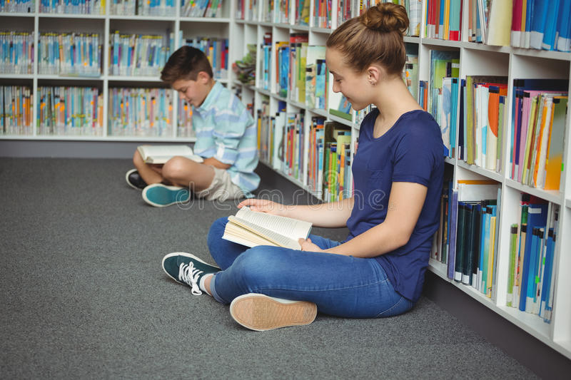 School kids reading books in library at school. Attentive school kids reading books in library at school stock images