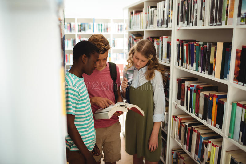 School kids reading books in library at school. Attentive school kids reading books in library at school stock photos