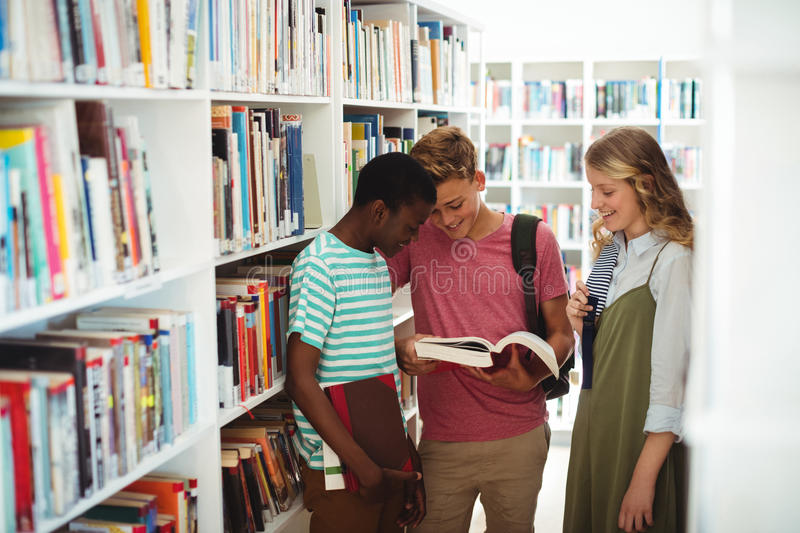 School kids reading books in library at school. Attentive school kids reading books in library at school royalty free stock photo