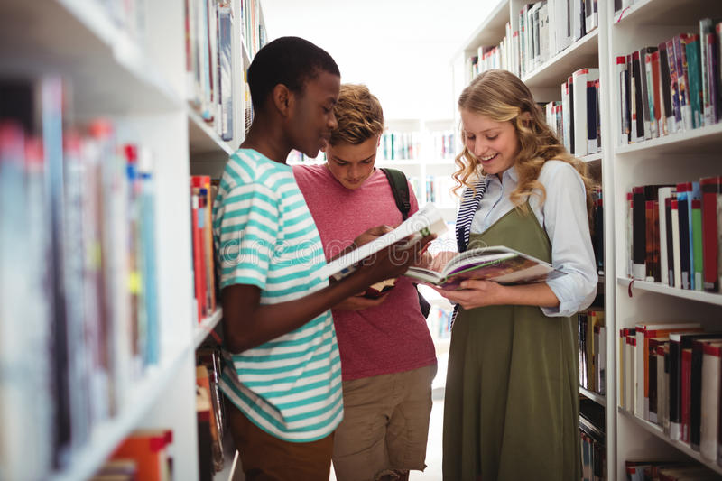 School kids reading books in library at school. Attentive school kids reading books in library at school stock image