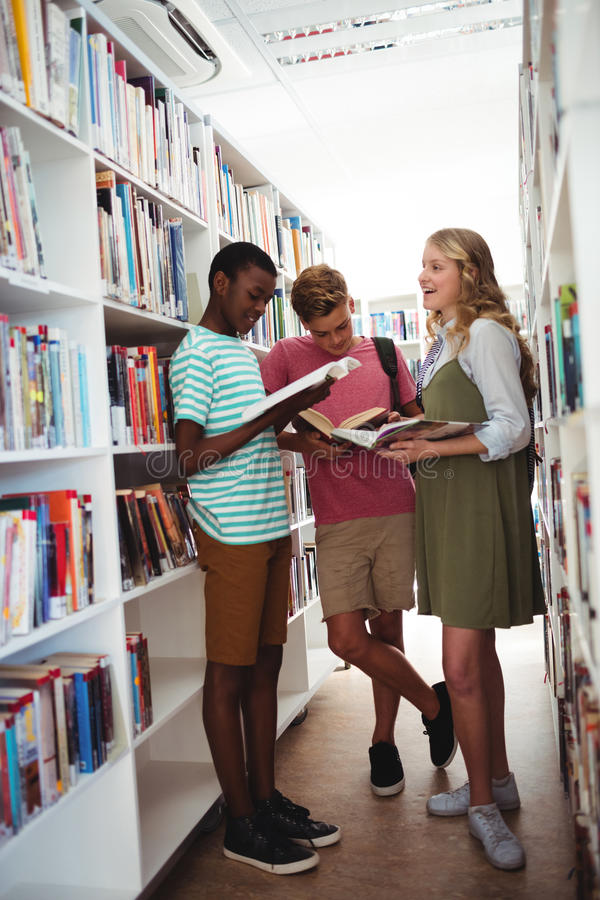 School kids reading books in library at school. Attentive school kids reading books in library at school stock photography
