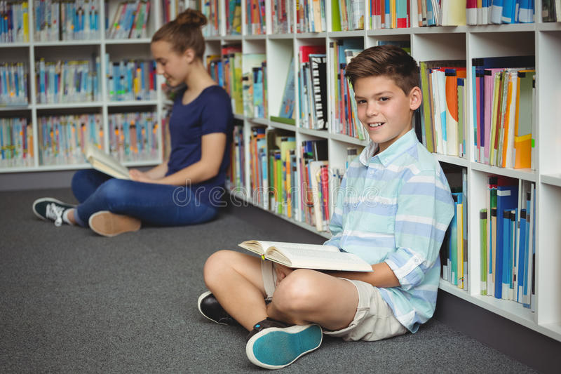 School kids reading books in library at school. Smiling school kids reading books in library at school royalty free stock photography