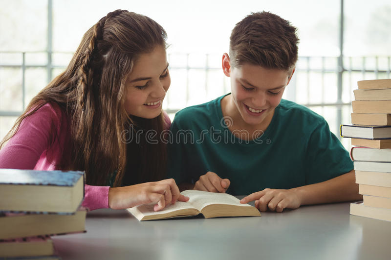 School kids reading books in library at school. Smiling school kids reading books in library at school royalty free stock photos