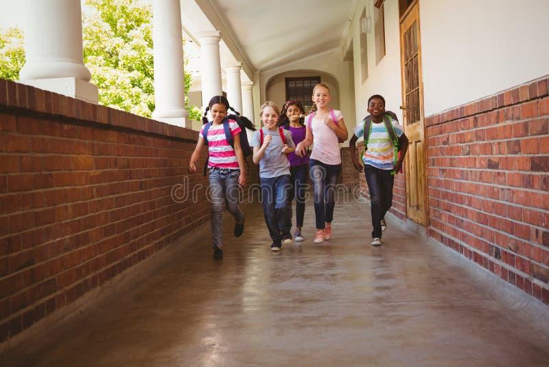 School kids running in school corridor royalty free stock photo