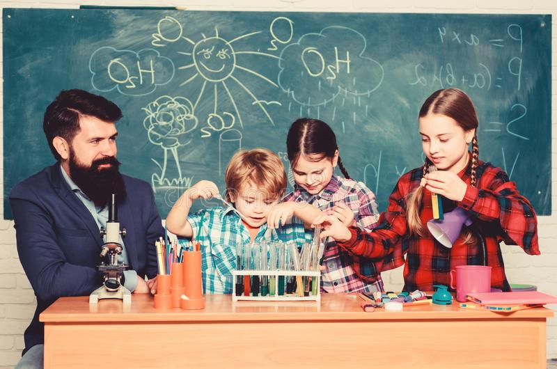 School kids scientist studying science. back to school. happy children teacher. Little kids learning chemistry in school stock photography