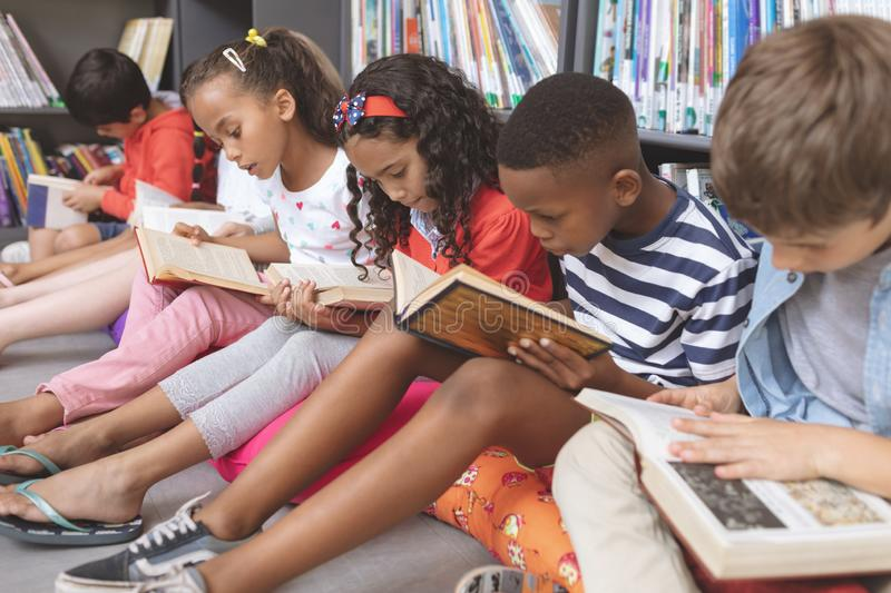 School kids sitting on cushions and studying over books in a library. Side view of mixte ethnicity school kids sitting on cushions and studying over books in a stock photo
