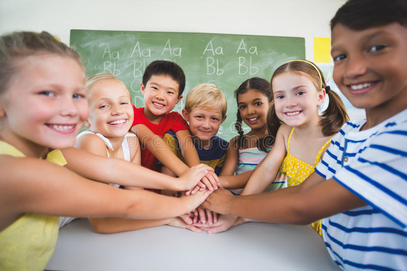 School kids stacking hands in classroom royalty free stock photos