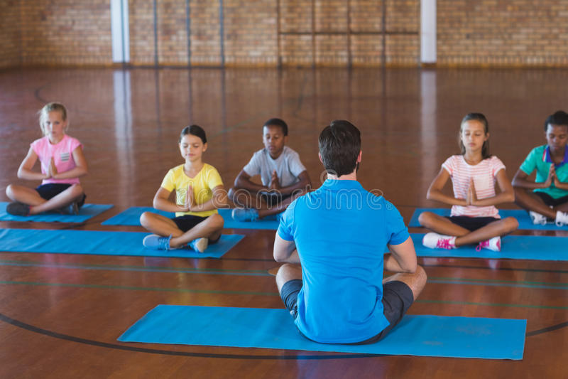 School kids and teacher meditating during yoga class royalty free stock image