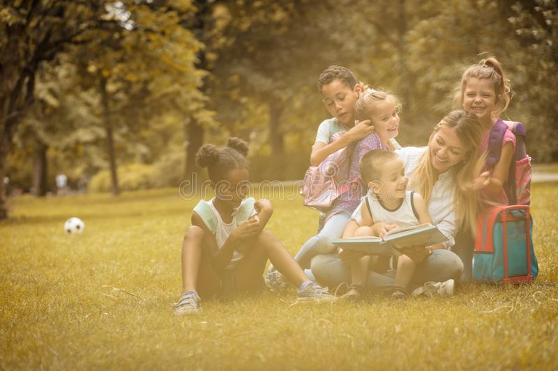 School kids and teacher at nature. Childhood. School kids and teacher at nature. Happy childhood stock photography
