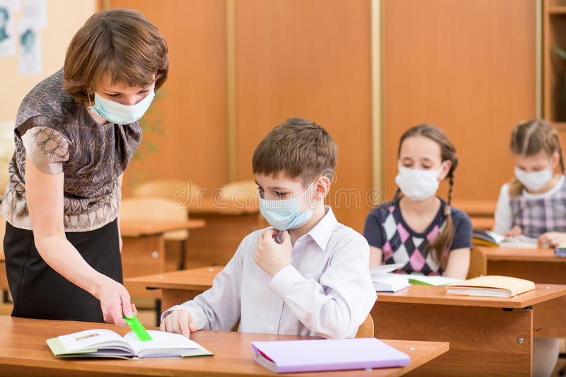 School kids and teacher with protection mask against flu. Virus at lesson royalty free stock image