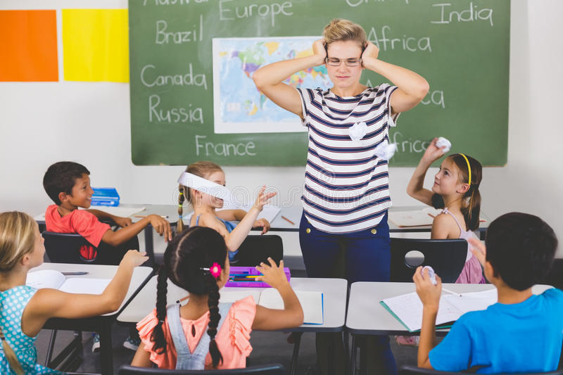 School kids throwing paper balls on teacher royalty free stock photos