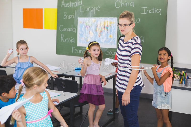 School kids tying up female teacher with rope in classroom royalty free stock images