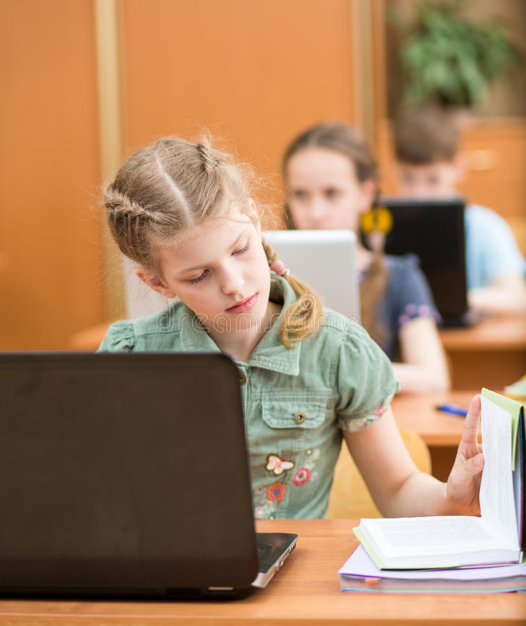 School kids using laptop at lesson royalty free stock image