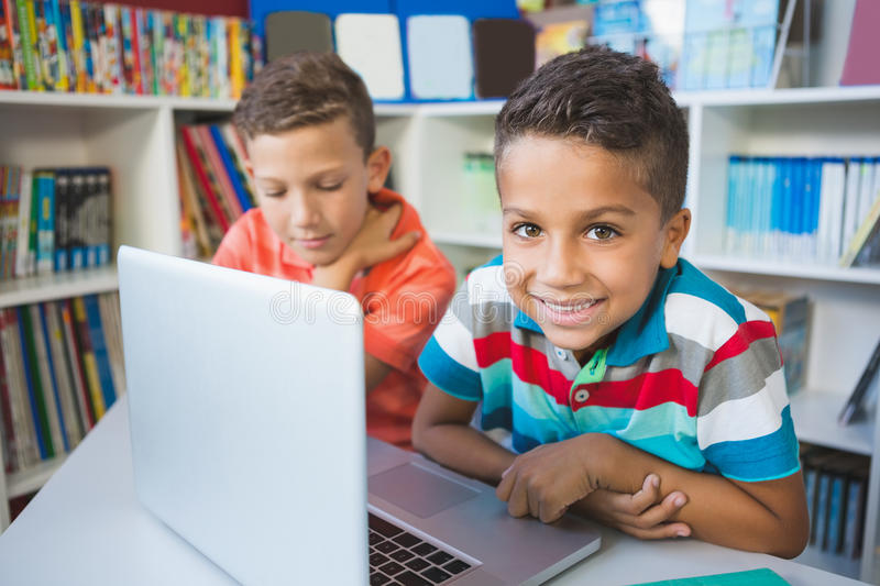 School kids using a laptop in library stock photography