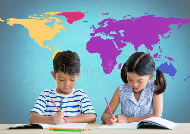 School kids writing at desk in front of colorful world map. Digital composite of School kids writing at desk in front of colorful world map stock images