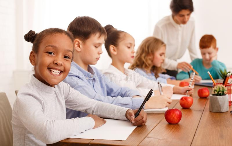 School kids writing test in classroom with teachers help stock photography