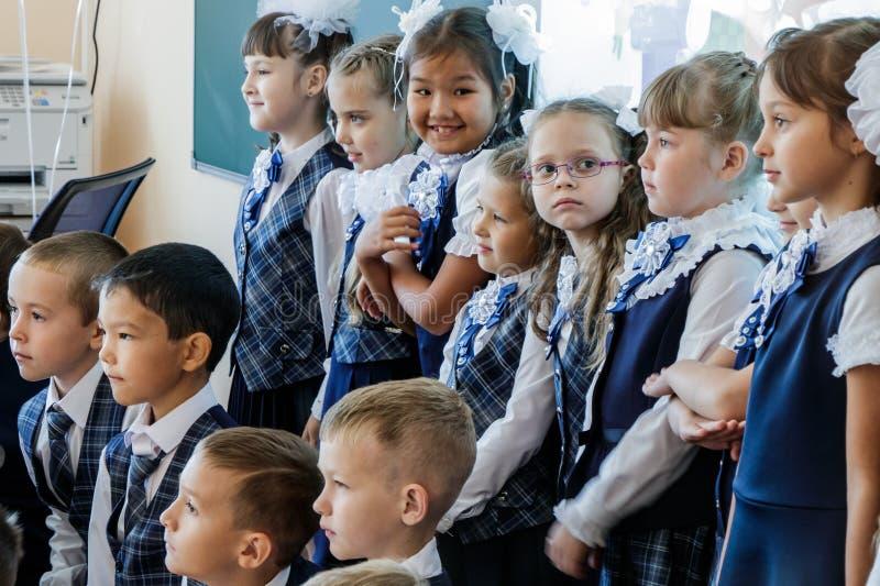 school Koele Zaal De kinderen in school eenvormige tribune in twee rijen en stellen voor een andere fotograaf Één meisje werd afg royalty-vrije stock fotografie