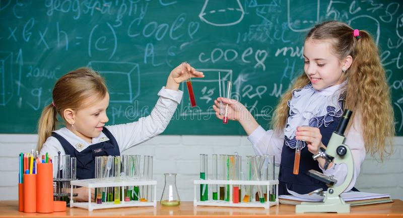 School laboratory partners. Kids busy with experiment. Chemical analysis and observing reaction. Test tubes with. Colorful substances. School equipment for royalty free stock image