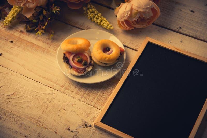 School leeg houten bord op houten vloer met hamburgerbrood en droge bloemen Onderwijs en Aardconcept Terug naar School royalty-vrije stock fotografie