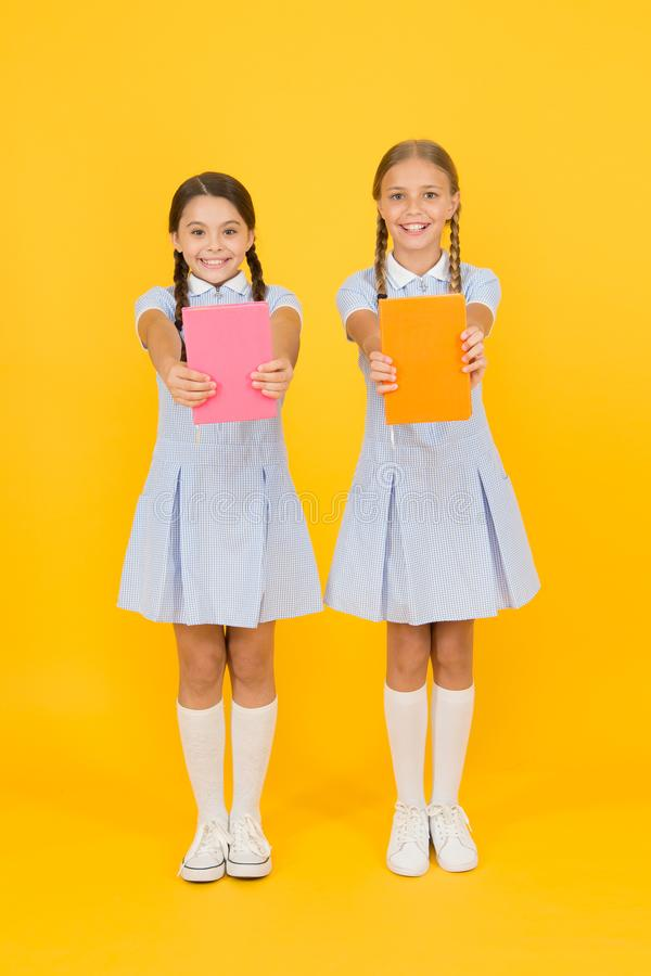 School library. Homeschooling concept. Literacy club. Cute children holding books on yellow background. Little girls. With encyclopedia or childrens books royalty free stock images