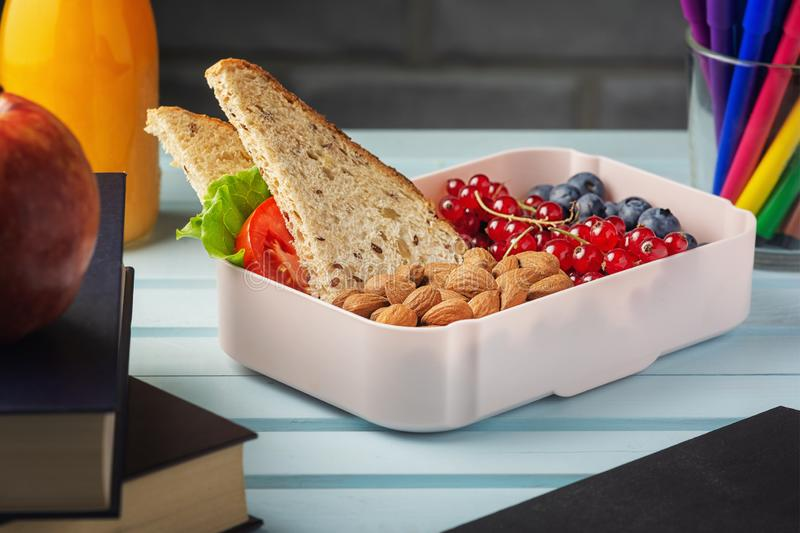 School lunch in a box, berries, nuts and a sandwich. Almonds, red currants and blueberries for a child s snack. Healthy stock photography