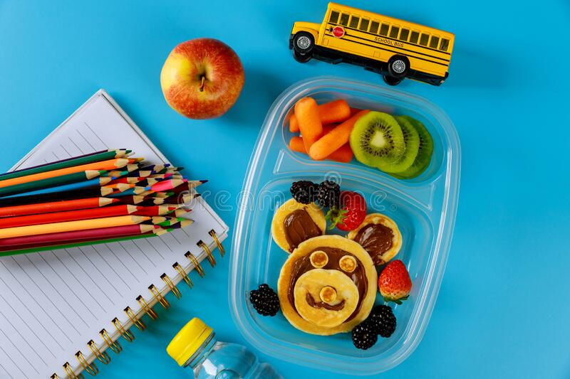 School lunch box with pancakes, fresh fruits and school bus toy. With supplies. Back to school concept royalty free stock image