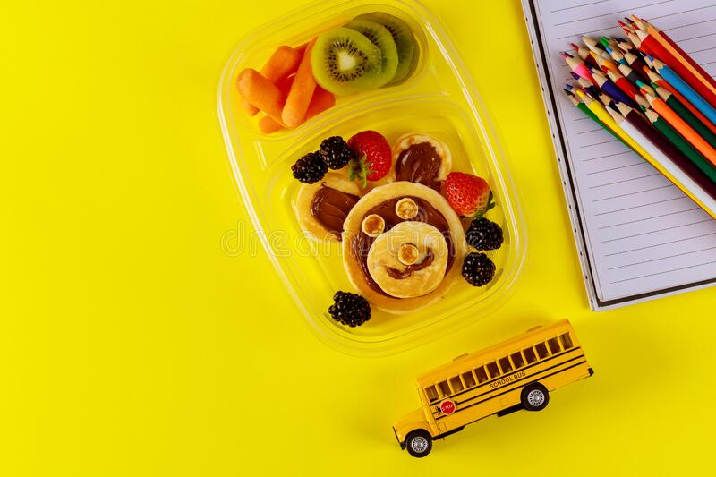 School lunch box with pancakes, fresh fruits and school bus toy. With supplies. Back to school concept royalty free stock photography