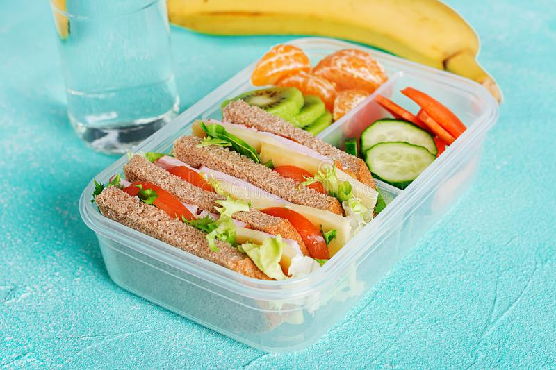 School lunch box with sandwich, vegetables, water, and fruits on table. stock photo