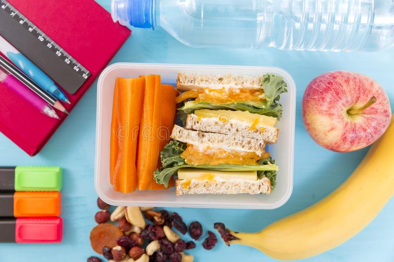 School lunch box. With sandwich, vegetables, water, nuts and fruits on turquoise background. Healthy eating habits concept stock images