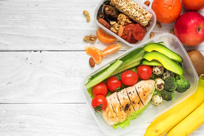 School lunch boxes with chicken, avocado, eggs and fresh vegetables, nuts and fruits on white wooden background stock images