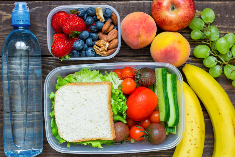 School lunch boxes with sandwich, fresh fruits and vegetables, berries and nuts and bottle of water royalty free stock images
